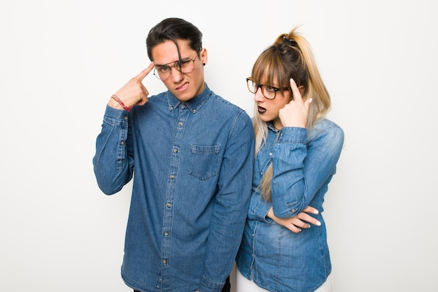 Young couple with glasses making the gesture of madness