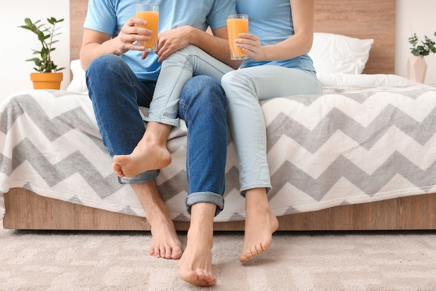 Молодая пара с бокалами сока, сидя на кровати у себя дома Premium Фотографии