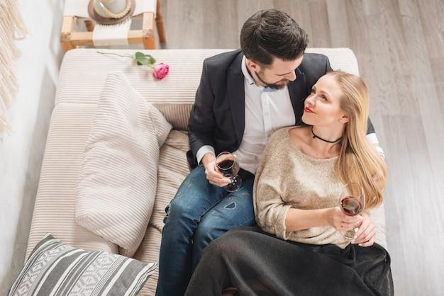 Молодая пара с бокалами вина, сидя на диване в комнате