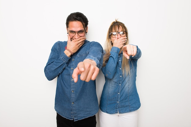 Young couple with glasses pointing with finger at someone and laughing