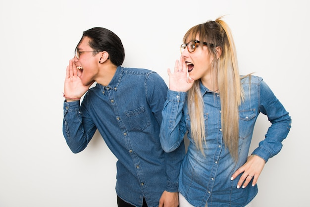 Young couple with glasses shouting with mouth wide open to the lateral