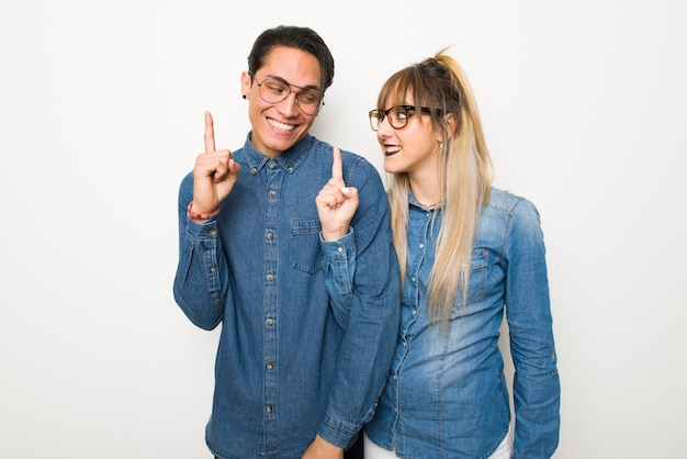 Young couple with glasses showing and lifting a finger in sign of the best