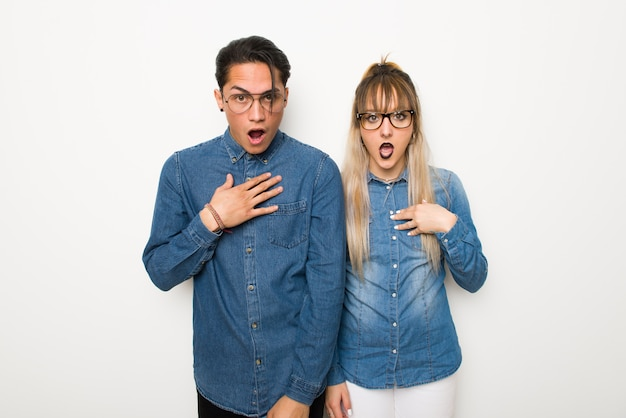 Young couple with glasses surprised and shocked while looking right