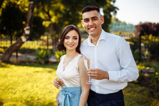 Young couple with glasses in their hands at the wedding celebration.