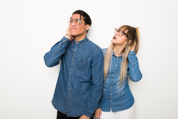 Young couple with glasses thinking an idea while scratching head