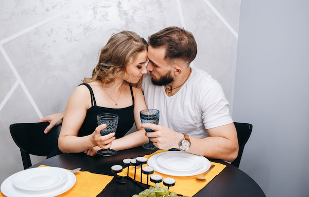 Young couple with glasses of wine having romantic dinner at table