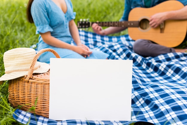 Young couple with guitar in park