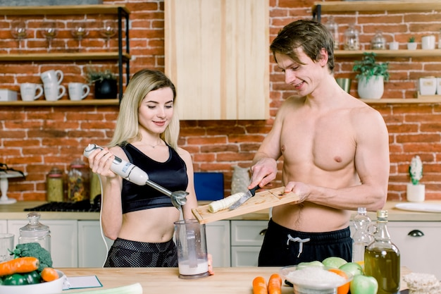 Young couple with hand blender making sweet milkshake smoothie in kitchen at home. drinking milk after workout. sport nutrition diet after gym. healthy lifestyle