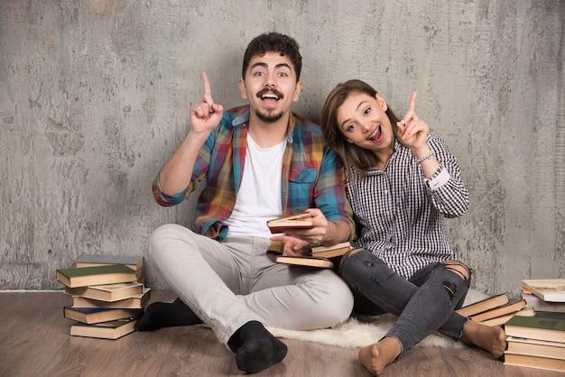 Giovani coppie con un libro interessante che punta al rialzo