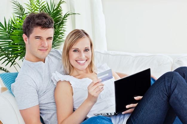 Молодая пара с ноутбуком и кредитной карты, онлайн в лежащей в гостиной