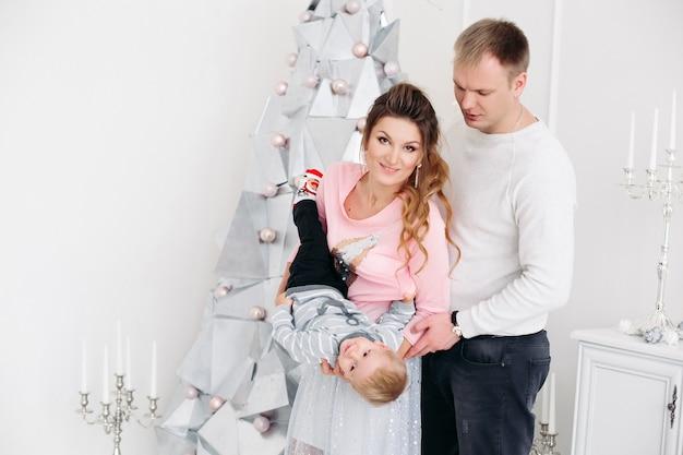크리스마스 스튜디오에 서서 정면을보고 포즈를 취하는 작은 아들과 함께 젊은 부부