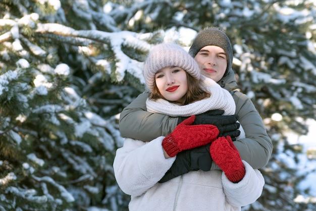 雪に覆われた森の背景に愛の抱擁を持つ若いカップル。