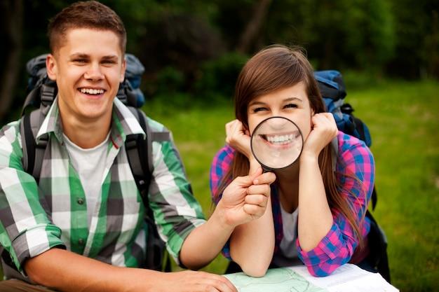 Молодая пара с картой в лесу