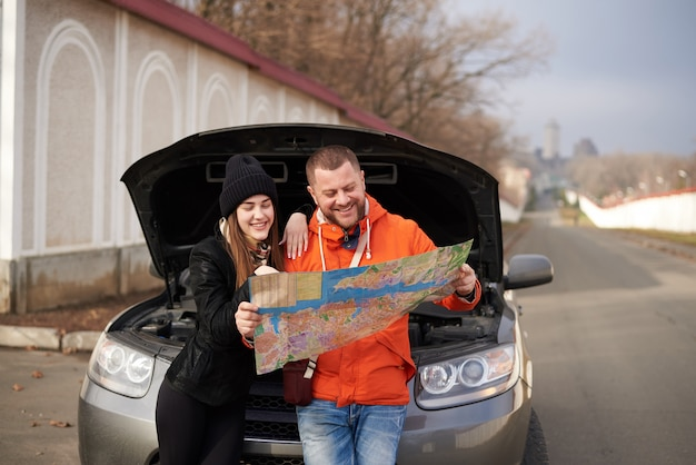 Young couple with a map near a car with an open hood.
