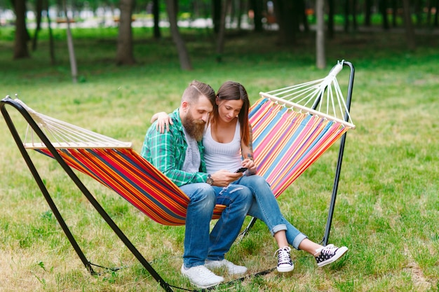 Young couple with mobile phone sitting on hammock