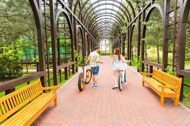 공원의 아치 밑의 통로에서 자유 시간을 보내는 현대적인 자전거를 탄 젊은 부부