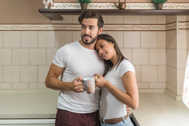 Young couple with mugs hugging in kitchen