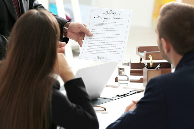 Young couple with notary at office