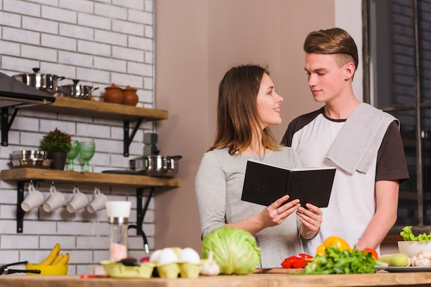 Young couple with notepad in kitchen