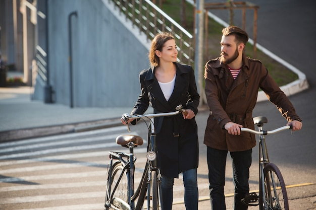 街の向かいの自転車で若いカップル