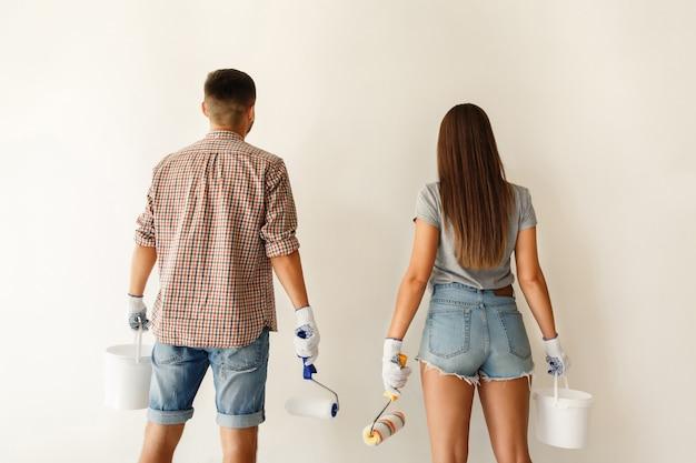 一緒に彼らの新しい家を改修する前に白い壁を見てペイントローラーと若いカップル