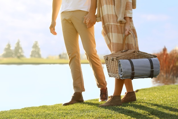 Young couple with picnic basket near lake on sunny day, closeup