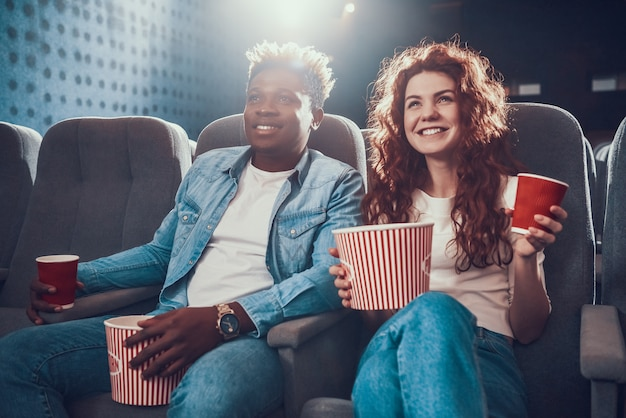 Young couple with popcorn sits in movie theater.