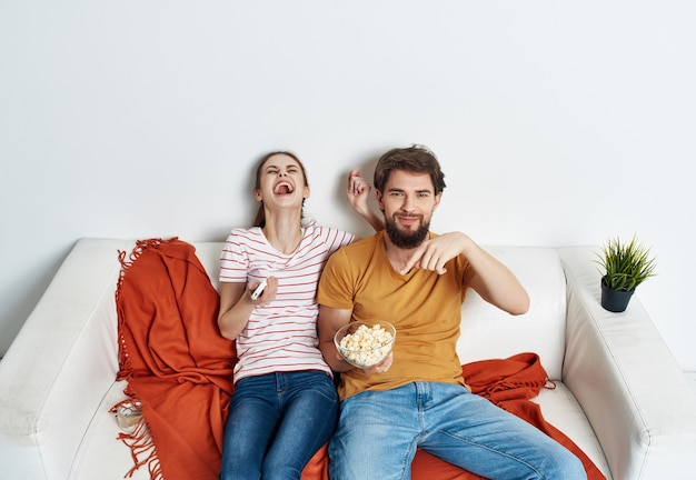 Young couple with popcorn sitting on the couch watching movie entertainment