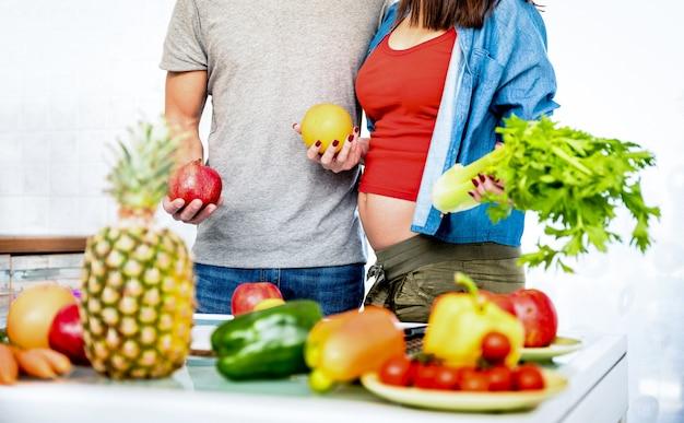 妊娠中の女性と若いカップルがキッチンで料理を準備する健康的なベジタリアン料理