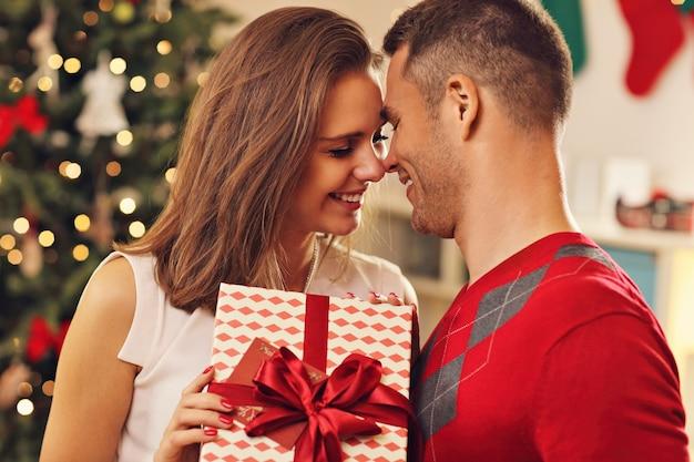 クリスマスツリーの上のプレゼントと若いカップル Premium写真