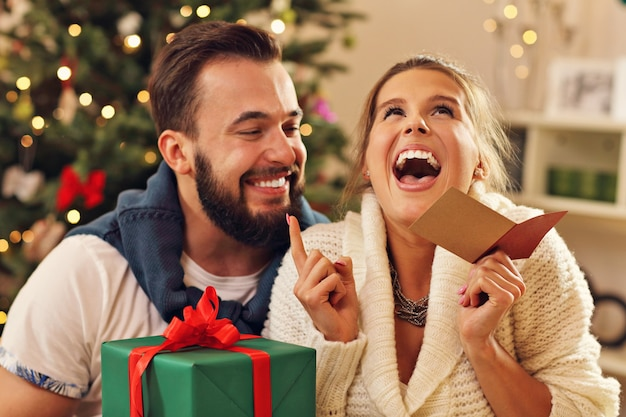クリスマスツリーの上のプレゼントと若いカップル