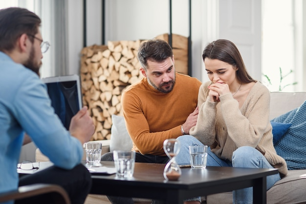 Young couple with problem on reception for family psychologist.