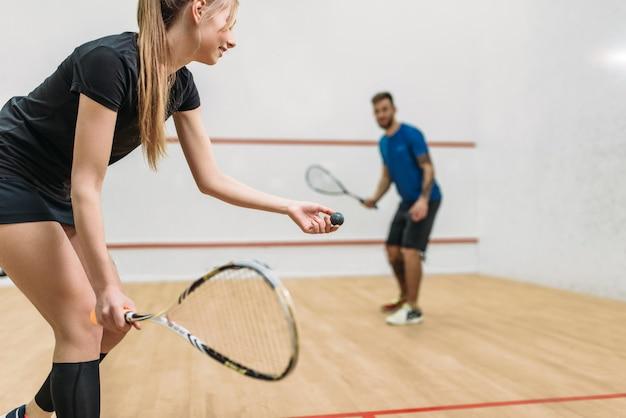 Молодая пара с ракетками играет в сквош в закрытом тренировочном клубе.