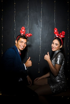 Young couple with red deer antlers headbands