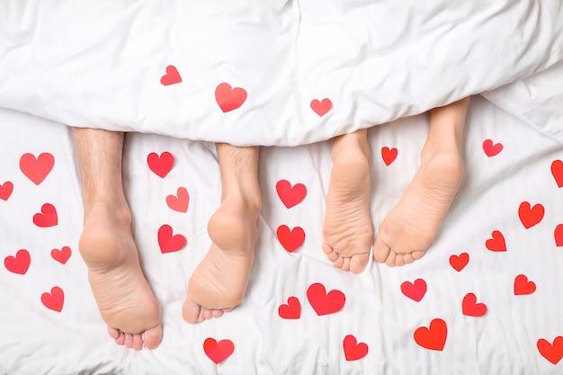 Молодая пара с красными сердцами, лежа в постели, вид сверху