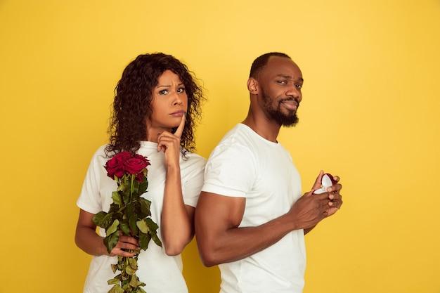 バラと結婚指輪の若いカップル