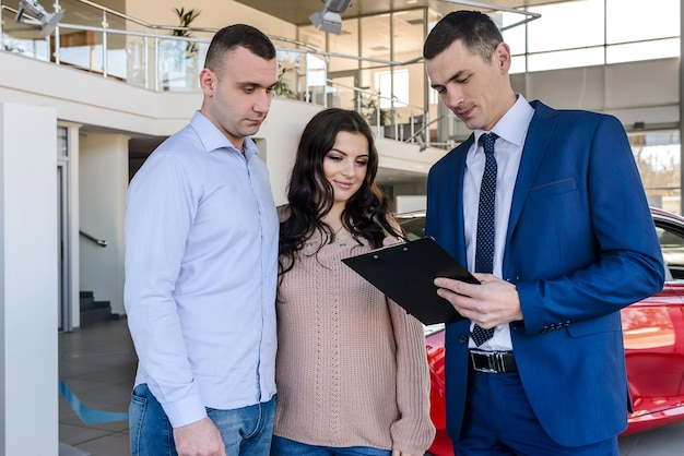 Young couple with salesman near new car signing contract