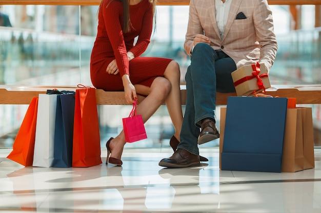 Молодая пара с хозяйственными сумками, отдыхая в торговом центре