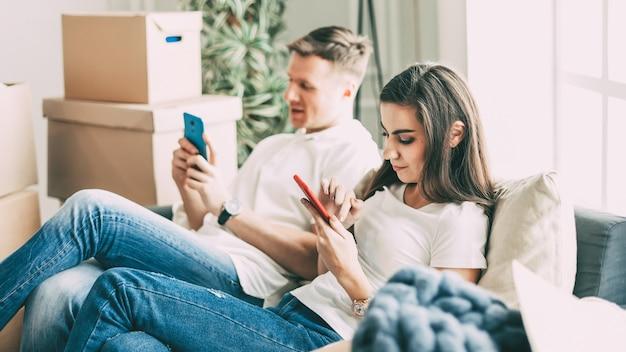 Молодая пара со смартфонами, сидя на диване в новой квартире