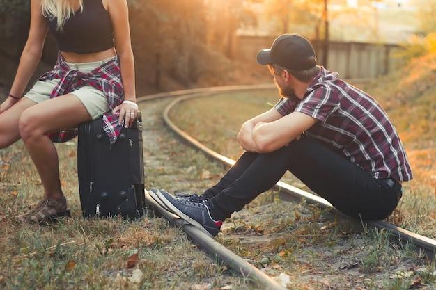 기차에 늦게 여행 가방을 든 젊은 부부 연인들이 레일에서 기차를 기다리고 있습니다