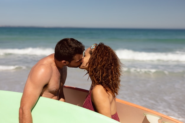 Young couple with surfboard kissing each other on beach in the sunshine