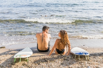 Young couple with surfboards relaxing on beach