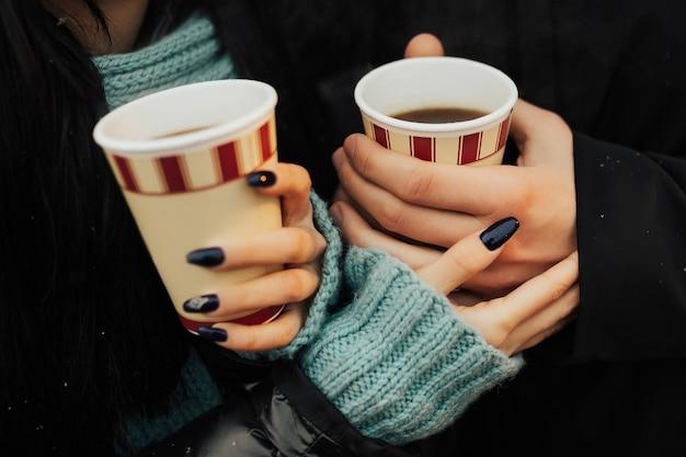 通りで手をつないでコーヒーをテイクアウトと若いカップル