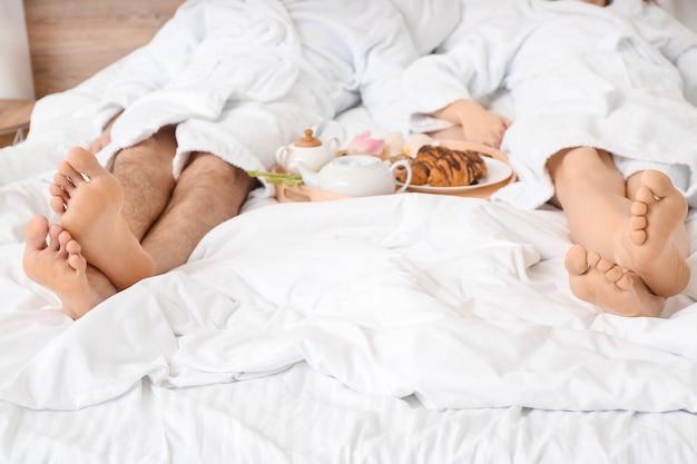 Молодая пара с вкусным завтраком в постели у себя дома