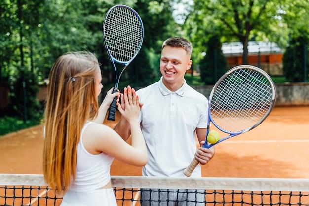 테니스 라켓을 들고 코트에 서서 서로 손을 잡고 있는 젊은 부부.
