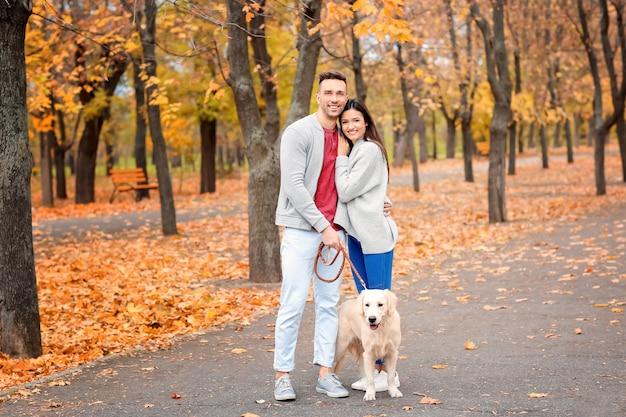 Молодая пара с собакой в парке