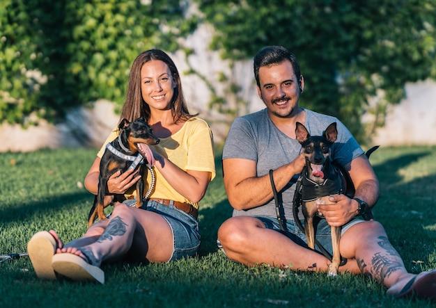 Молодая пара с собаками сидит, глядя в камеру в парке. вид спереди пара, сидящая на траве со своими собаками в солнечный день.