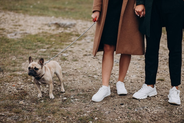 Young couple with their french bulldog in park