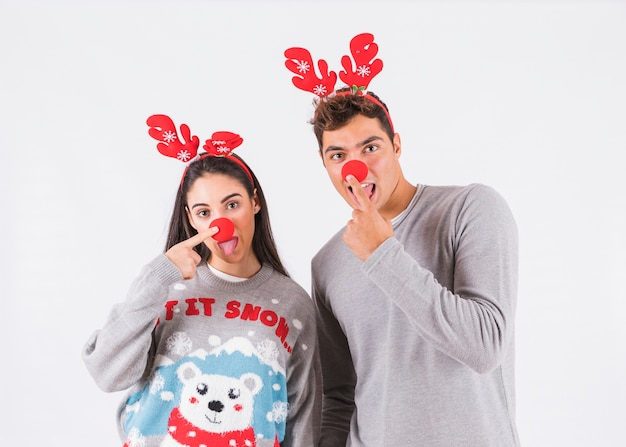 Young couple with tongue out, deer antlers headbands and funny noses
