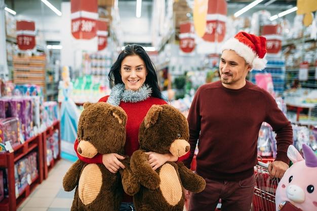 두 개의 큰 봉제 곰과 함께 젊은 부부, 슈퍼마켓에서 크리스마스 선물 구입